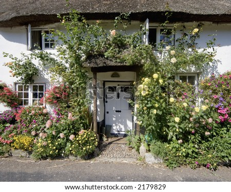 thatched cottage with flowers doorway white village - stock photo