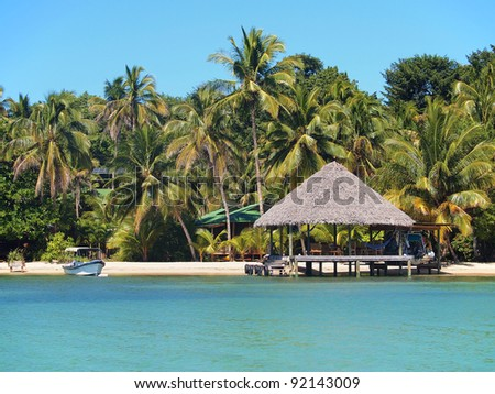 Thatched hut on tropical beach with houses hidden by coconut trees in background, Caribbean sea, Panama - stock photo