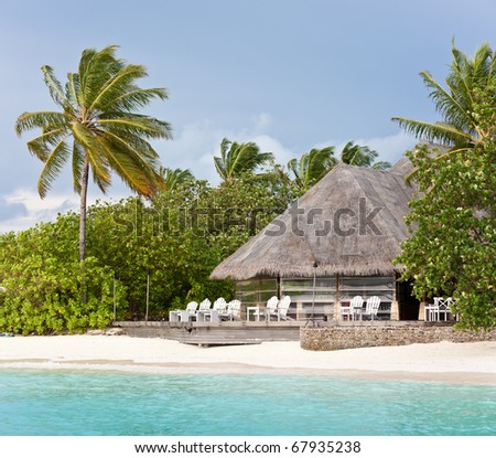 thatched lounge bar on the beach of maldives island resort - stock photo