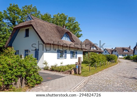 thatched-roof house settlements with trees, cobbled stone street aside - stock photo
