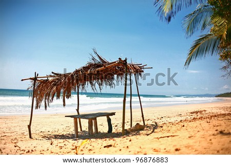 Thatched roof over table on beach of Costa Rica - stock photo