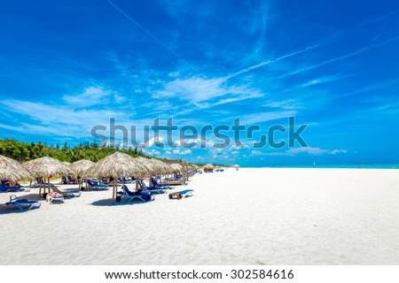 Thatched umbrellas on a beautiful summer day on the beach - stock photo