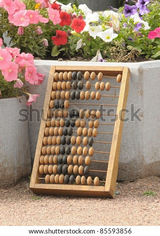 The abacus which is standing near a bed with flowers - stock photo