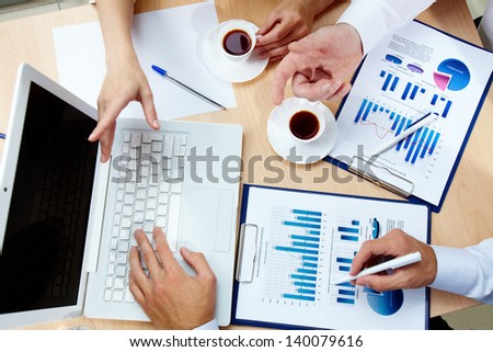 The above view of business people discussing financial data - stock photo