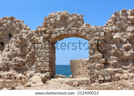 The Acre surrounding wall gate with small view of the mediterranean sea water  - stock photo