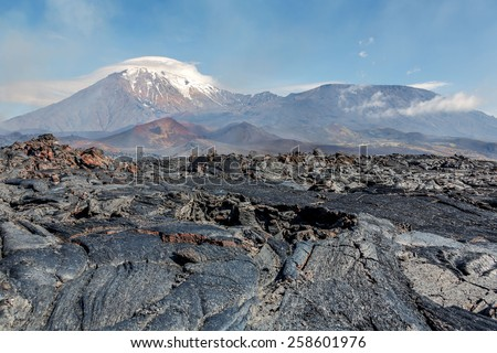 The active lava flow from a new crater on the slopes of volcanoes Tolbachic (background volcanoes Tolbachic Sharp (left) and Tolbachic Flat (right) - Kamchatka, Russia - stock photo