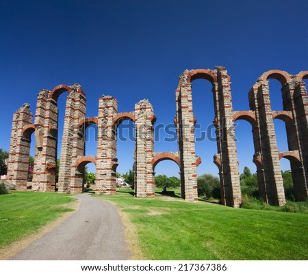 The Acueducto de los Milagros (English: Miraculous Aqueduct) is a ruined Roman aqueduct bridge, part of the aqueduct built to supply water to the Roman colony of Emerita Augusta, today Merida, Spain. - stock photo