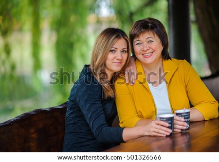 the adult daughter embraces the elderly mother and and together smile, relations between the senior and younger generation, close-knit family