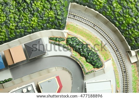 The aerial miniature plastic model of town scene represent the plastic toy train and miniature town model background concept related idea.
