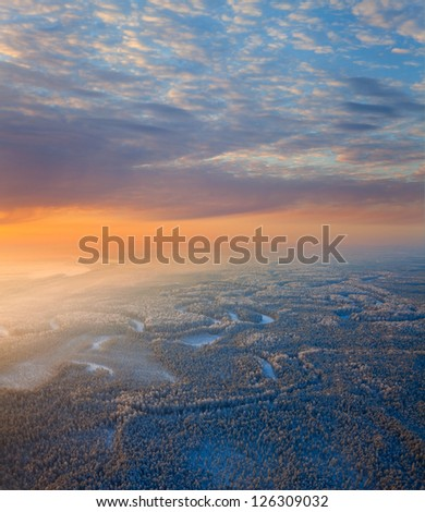 The Aerial view of snow-covered forest in time of sunny winter evening. Crowns of coniferous trees are lighted up by a bright setting sun. - stock photo