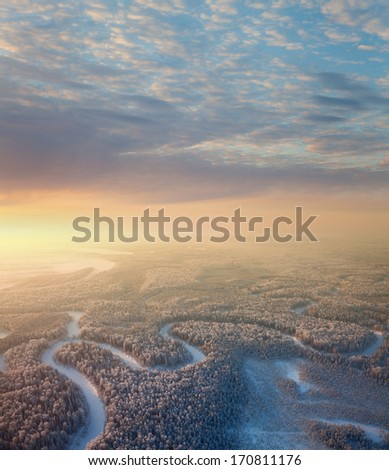 The Aerial view the river on snow-covered forest plain in time of cloudy winter evening. Crowns of coniferous trees are lighted up by a bright setting sun.  - stock photo