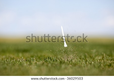 The after effects of a golf swing.  Shallow depth of field with motion blur on Tee - stock photo