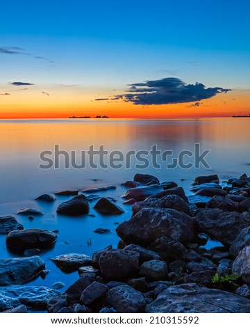 The afterglow of sunset paints the water and sky with intense and beautiful colors at Sister Bay, Wisconsin. - stock photo