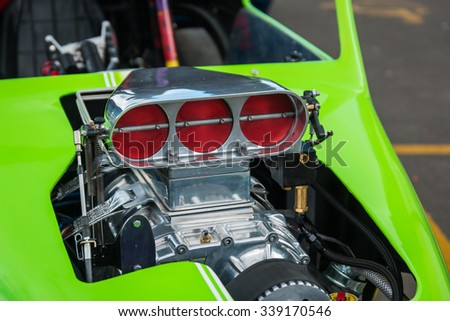 The air intake of a v8  in a green hot rod. - stock photo