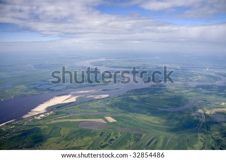 The Air view of greater river on the plain.