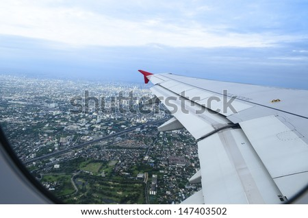 the airplane is taking off over city - stock photo