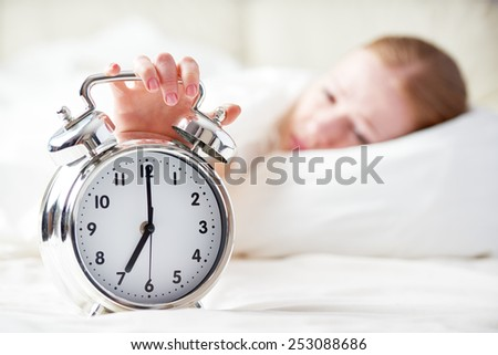 the alarm clock and a sleeping young woman - stock photo