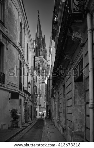 The alleys in the historic center of Montpellier, France are very narrow and scenic. They are inviting people to have a walk. In the background is the tower of St. Roch visible. - stock photo
