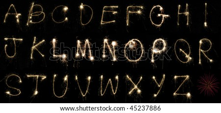 The alphabet spelled out by hand using sparklers at night on long exposure. Can be cropped to spell out any word or message. - stock photo