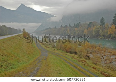 The Alpine section of the river Rhine in Switzerland, near to the border with Liechtenstein. Landscape taken on a misty day in the Fall