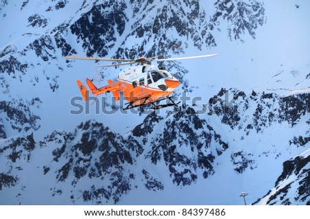 "THE ALPS, ITALY - CIRCA FEB 2011:A Pelikan Rescue Helicopter of ""Elisoccorso Provinciale Sudtirolo"" flies through the mountains in South Tirol in search of avalanche victims CIRCA FEB 2011 in The Alps - stock photo"