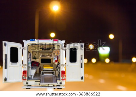 The ambulance, blur image of road at night as background. - stock photo
