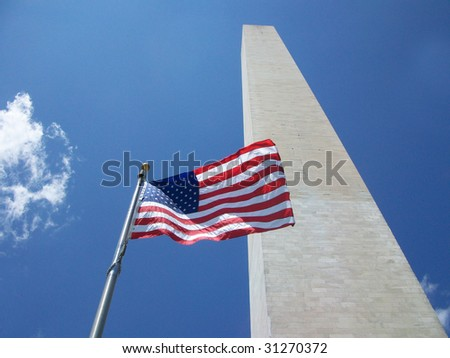 The American Flag flying in front of the Washington Monument. - stock photo