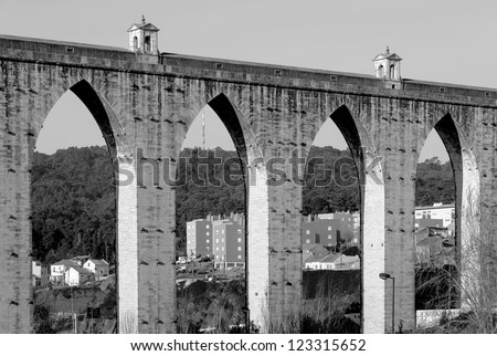The ancient aqueduct in the Lisbon built in 18th century, Portugal (black and white) - stock photo