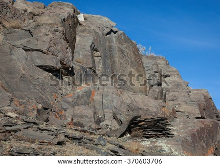 The ancient drawings on rocks in the mountains - stock photo
