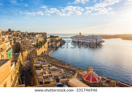 The ancient walls of Valletta and Malta harbor with cruise ship in the morning - Malta - stock photo