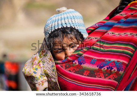 THE ANDES, PERU - MAY 30, 2012: Quechua baby in a village in the mountains of The Andes over Ollantaytambo, Peru - stock photo