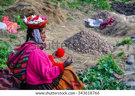 THE ANDES, PERU - MAY 30, 2012: Quechua woman working in a village in the mountains of The Andes over Ollantaytambo, Peru - stock photo