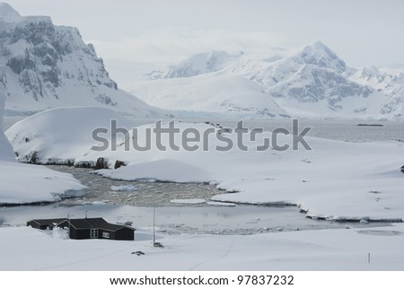The Antarctic winter station on the background of mountains and ocean. - stock photo