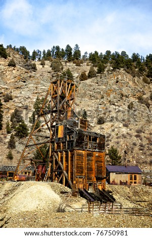 The antique remains of a century old gold mine clings to the side of a wilderness hill. - stock photo