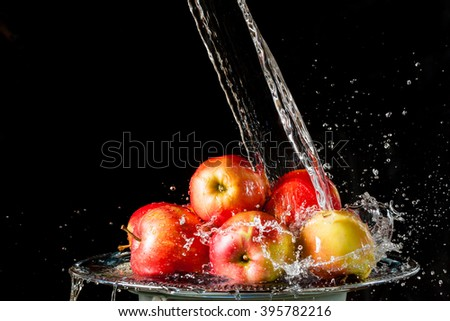 The apples lying on a silver top and falling water on a black background - stock photo