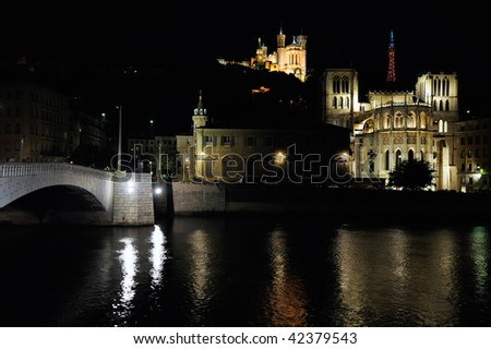 The apse of the Saint Jean cathedral, next to the Saone river, is dominated by the Fourviere basilica. - stock photo