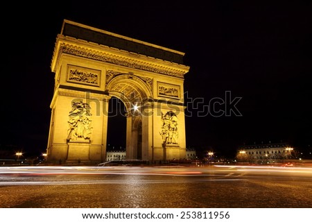 The Arc de Triomphe Paris illuminated by night, the most monumental of all triumphal arches. The Arch of Triumph is in honor of those who fought for France during the Napoleonic Wars. Long exposure. - stock photo