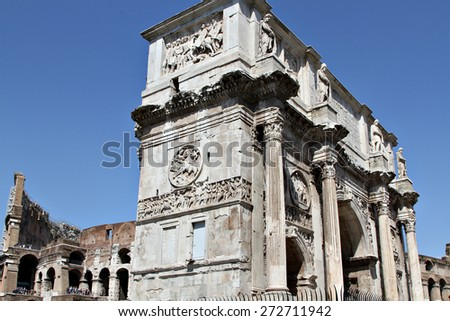 The Arch of Constantine (Arco Constantino), a ruin of the ancient Roman empire stands alongside the Colosseum in Rome, Italy. - stock photo