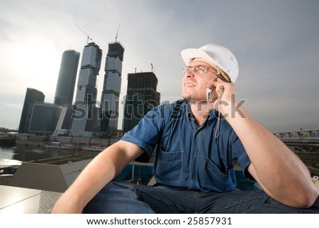 The architect wearing a protective helmet sitting in front of a building site and speaking over mobile phone