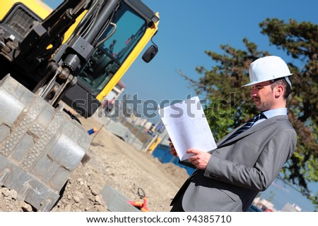 the architect with hardhat on building site - stock photo
