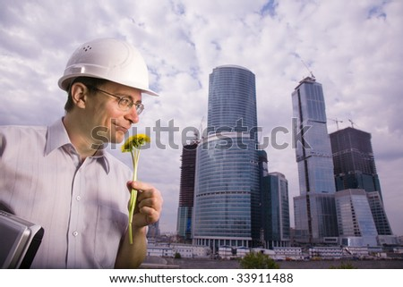 The architect with laptop in hands wearing protective helmet standing in front of a building site and smelling dandelion flowers