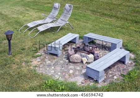 The area for a barbecue on a green grass of a garden meadow. Wooden handmade  benches are painted with gray paint. The brazier is made of granite stones. The lamp will light a night party - stock photo