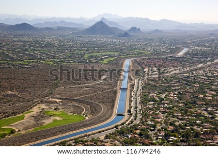 The Arizona Canal flowing past suburbs and golf courses in Scottsdale, Arizona - stock photo
