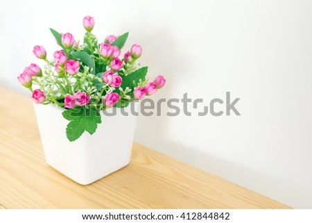 the artificial pink flower in the pot at the wooden table with the white wall background - stock photo