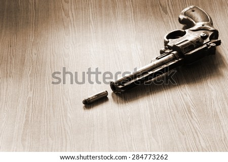 The artificial vintage plastic toy gun beside artificial bullet shape toy on sepia tone represent crime science investigation instrument concept related idea - stock photo