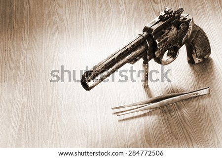 The artificial vintage plastic toy gun beside forceps on sepia tone represent crime science investigation instrument concept related idea - stock photo