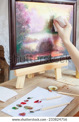 The artist paints a picture of the landscape using oil paints mounted on an easel. Selective focus - stock photo