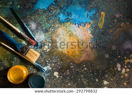 The artist's palette. Spray droplets and smears on a dark background. Nearby are open cans of paint and brushes. - stock photo