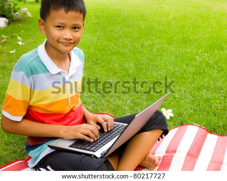 The asian boy happy with notebook on green grass at backyard - stock photo