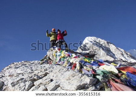 The Asian couple on the top of Kala Patthar of Himalayas in Nepal